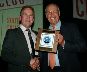 "Former Los Angeles Press Club President, Bill Rosendahl, presents Collins with a ""cheeseboard"" slang for the First Place plaque that winners take home from the annual gala."