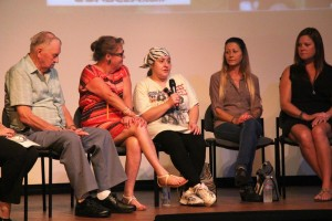 Denise Dardarian with microphone with Ralph Powell, far left, and other survivors.