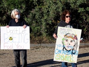 'Don't Let Boeing Fool You' and 'Burn Your Shoes Your On Contaminated Grounds' protest signs at SSFL